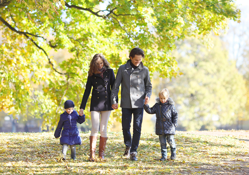 Family walking through leaf-covered ground